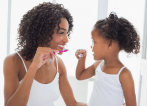 mum-showing-little-girl-how-to-brush-teeth-properly-to-avoid-bad-breath