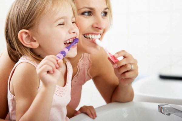 child-and-parent-brushing-teeth-together